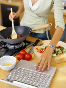 young woman cooking food and using a laptop in the kitchen